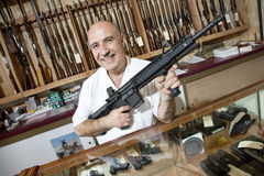 Portrait of a happy mature merchant with rifle in gun shop Stock Photos