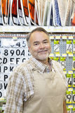 Portrait of a happy mature salesperson in hardware store Royalty Free Stock Images