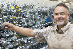 Portrait of a happy mature salesperson holding metallic equipment in hardware store Royalty Free Stock Photography