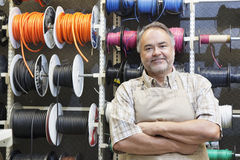 Portrait of a happy mature salesperson standing in front of electrical wire spool with arms crossed in hardware store stock photography