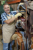 Portrait of a happy mature salesperson standing by horse riding tack in feed store Royalty Free Stock Images