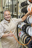 Portrait of a happy mature store clerk with electrical wire spool in hardware shop Stock Photos