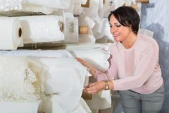 Portrait of happy mature woman with cloth rolls. Portrait of charming positive smiling mature woman with cloth rolls  in textile store Stock Image