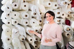 Portrait of happy mature woman with cloth rolls Stock Photos