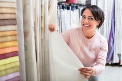 Portrait of happy mature woman with cloth specimens. Portrait of happy smiling mature woman with cloth specimens in textile store stock photos