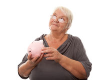 Portrait of a happy mature woman holding piggy bank isolated aga Stock Photo