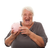 Portrait of a happy mature woman holding piggy bank isolated aga Stock Images