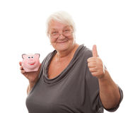 Portrait of a happy mature woman holding piggy bank isolated aga Stock Image