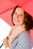 Portrait of happy mature woman holding red umbrella Royalty Free Stock Photo