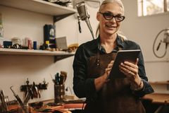 Jewelry maker using digital tablet in her workshop stock images