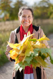Portrait of  happy mature woman with maple posy Stock Photos