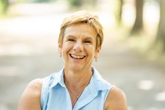 Portrait of a happy mature woman in the park. Emotion, age and people concept - portrait of happy senior woman laughing in the park Stock Photos