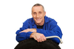 Portrait of happy mechanic with a tire and wrench Royalty Free Stock Photography