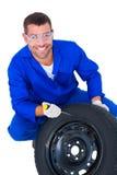 Portrait of happy mechanic working on tire stock photo