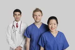 Portrait of happy medical team standing over gray background Stock Photo