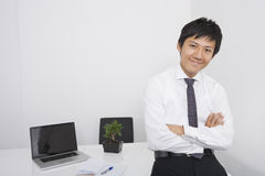 Portrait of happy mid adult businessman with arms crossed leaning on office desk Stock Images
