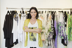 Portrait of a happy mid adult woman with arms crossed in front of clothes rack Stock Photography