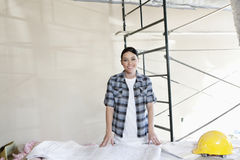 Portrait of a happy mid adult woman with building plans at construction site Stock Images