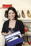 Portrait of a happy mid adult woman with footwear box in shoe store Royalty Free Stock Photos