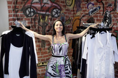 Portrait of a happy mid adult woman standing by clothes rack with graffiti in background Royalty Free Stock Image