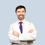 Portrait of happy middle-aged dentist on a pale background, wear Royalty Free Stock Image