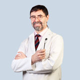 Portrait of happy middle-aged dentist on a pale background, wear Royalty Free Stock Images