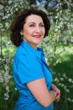 Portrait of happy middle aged woman walking in blooming garden Stock Image