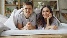 Portrait of happy mixed-race couple emerging from under the blanket, smiling and looking at camera. Happy married life. Attractive people and romantic stock footage