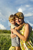 Portrait of happy mom kissing and shake son on green summer garden. Cute  mother embracing baby boy looking at camera Royalty Free Stock Image