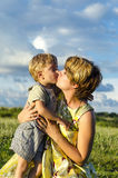 Portrait of happy mom kissing and shake son on green summer garden. Royalty Free Stock Photography