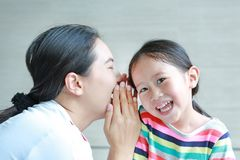 Portrait of happy mom whispering a something secret to her little daughter ear on sofa at home. Mother and kid communication royalty free stock images