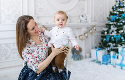 Portrait of happy mother and adorable baby against domestic festive backdrop with Christmas tree Royalty Free Stock Photos