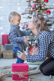 Portrait of happy mother and adorable baby celebrate Christmas. New Year`s holidays. Toddler with mom in the festively decorated r stock images
