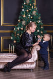 Portrait of happy mother and adorable baby celebrate Christmas. New Year`s holidays. Toddler with mom in the festively decorated r royalty free stock images