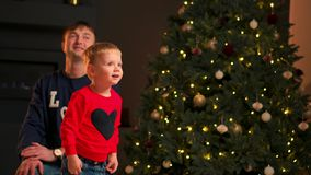 Portrait of happy mother and adorable baby celebrate Christmas. New Year`s holidays. Toddler with mom in the festively stock video footage