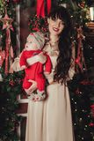 Portrait of happy mother and adorable baby in suit of Santa`s little helper.  Royalty Free Stock Photography