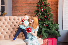 Portrait of happy mother and adorable son holding bauble against domestic festive backdrop with Christmas tree Stock Photography