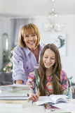 Portrait of happy mother assisting daughter in doing homework at table Stock Photos