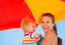 Portrait of happy mother and baby on beach Stock Image