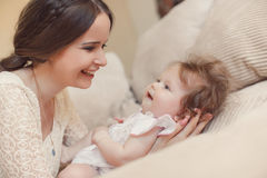 Portrait of happy mother with baby on the bed Royalty Free Stock Photo
