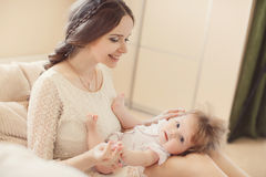 Portrait of happy mother with baby on the bed Stock Photo
