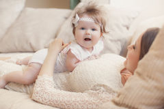 Portrait of happy mother with baby on the bed Stock Photos