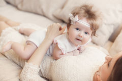 Portrait of happy mother with baby on the bed Royalty Free Stock Image