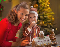 Portrait of happy mother and baby eating cookie in kitchen Royalty Free Stock Images