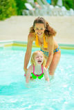 Portrait of happy mother and baby girl inpool Royalty Free Stock Photo