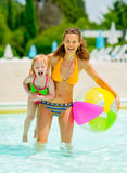 Portrait of happy mother and baby girl in pool Royalty Free Stock Photos