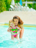 Portrait of happy mother and baby girl in pool Royalty Free Stock Images