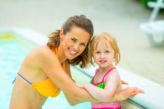 Portrait of happy mother and baby girl in pool Royalty Free Stock Photography