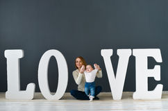 Portrait  happy mother and baby,on gray background near large letters of the word love Royalty Free Stock Photo