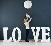 Portrait  happy mother and baby,on gray background near large letters of the word love Stock Photos